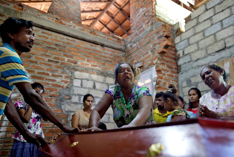 Lalitha, center, weeps over the coffin of her 12-year old niece, Sneha Savindi, who was a victim of the Easter Sunday bombing at St. Sebastian Church, after being brought home in Negombo, Sri Lanka, Monday, April 22, 2019. Easter Sunday bombings of churches, luxury hotels and other sites was Sri Lanka's deadliest violence since a devastating civil war in the South Asian island nation ended a decade earlier. (AP Photo/Gemunu Amarasinghe)