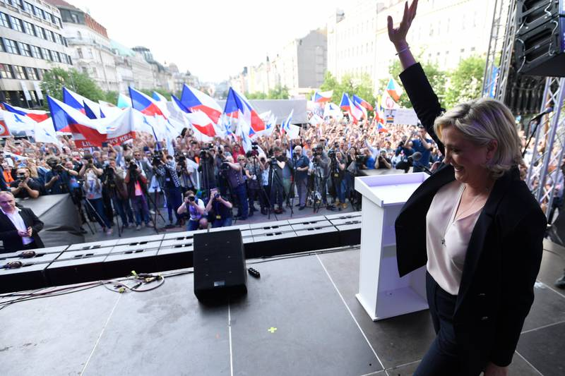 """Leader of the French National Front Marine Le Pen waves as she arrives on stage during the rally against """"dictate of the European Union"""" organized by Czech far-right Freedom and Direct Democracy party (SPD) in Prague, Czech Republic, Thursday, April 25, 2019. (Michal Kamaryt/CTK via AP)"""